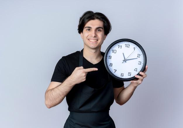 Sorridente giovane barbiere maschio bello in tenuta uniforme e punti all'orologio di parete isolato su bianco