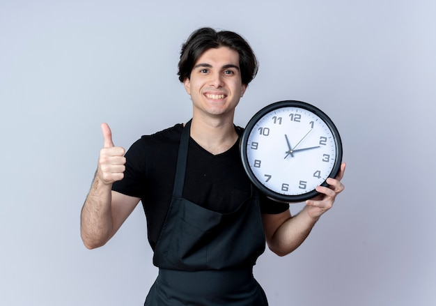 Sorridente giovane barbiere maschio bello in uniforme che tiene l'orologio di parete il suo pollice in su isolato su bianco