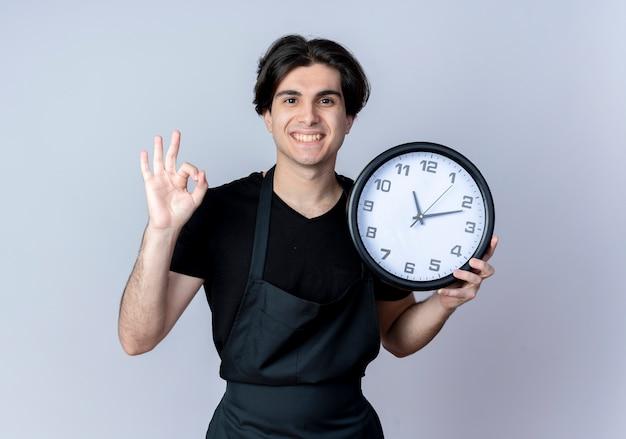Sorridente giovane barbiere maschio bello in uniforme che tiene l'orologio di parete e che mostra okey gesto isolato su bianco