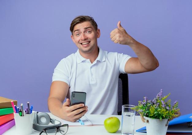 파란색에 고립 된 전화 그의 엄지를 들고 학교 도구와 책상에 앉아 웃는 젊은 잘 생긴 남자 학생