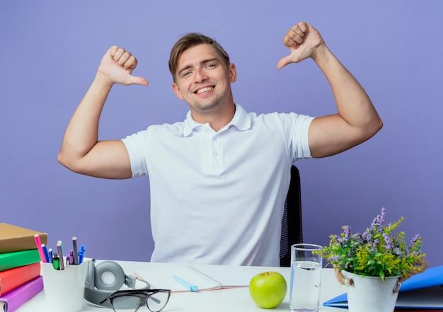 학교 도구로 책상에 앉아 웃는 젊은 잘 생긴 남자 학생 자신이 파란색에 고립 된 포인트