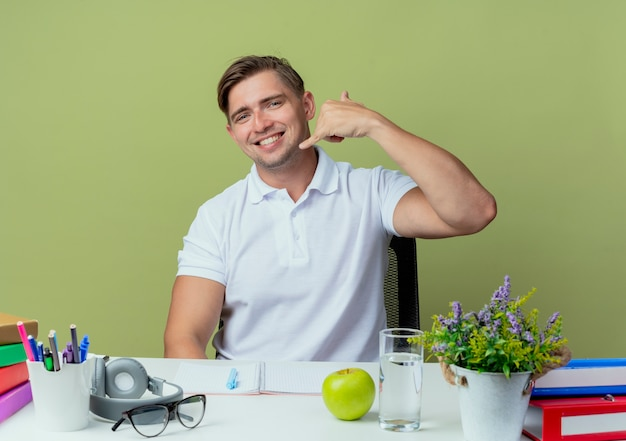 Sorridente giovane studente maschio bello seduto alla scrivania con gli strumenti della scuola che mostra il gesto di telefonata isolato su verde oliva