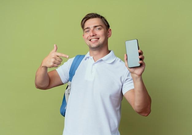 Улыбающийся молодой красивый студент-мужчина в спине держит сумку и указывает на телефон, изолированный на оливково-зеленом