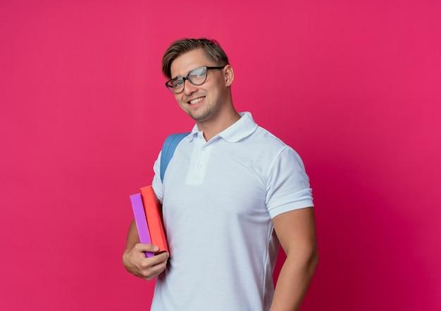 Sorridente giovane studente maschio bello che indossa la borsa posteriore che tiene i libri isolati sul rosa