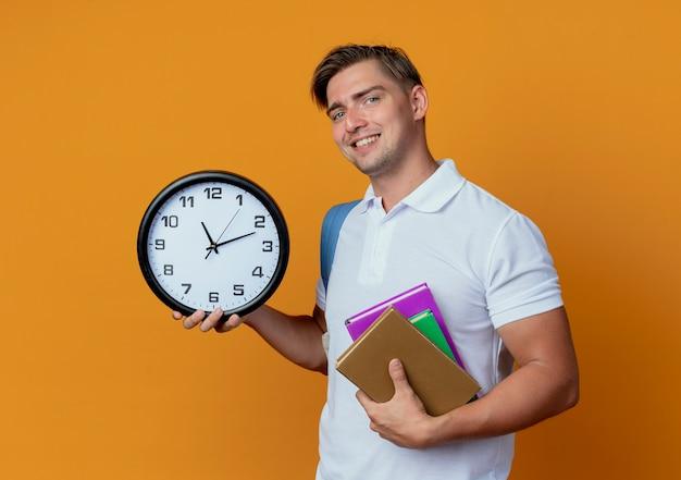 Sorridente giovane studente maschio bello che indossa la borsa posteriore con libri e orologio da parete