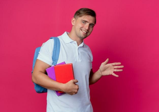 Sorridente giovane studente maschio bello che porta i libri della holding della borsa posteriore