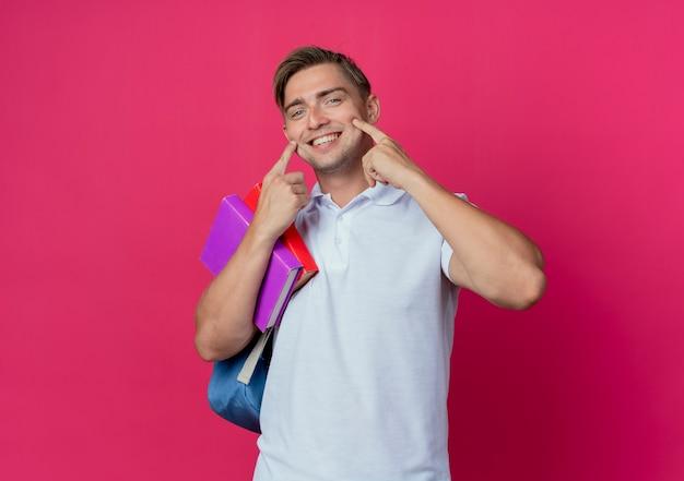 本を保持しているバックバッグを身に着けている若いハンサムな男性学生の笑顔