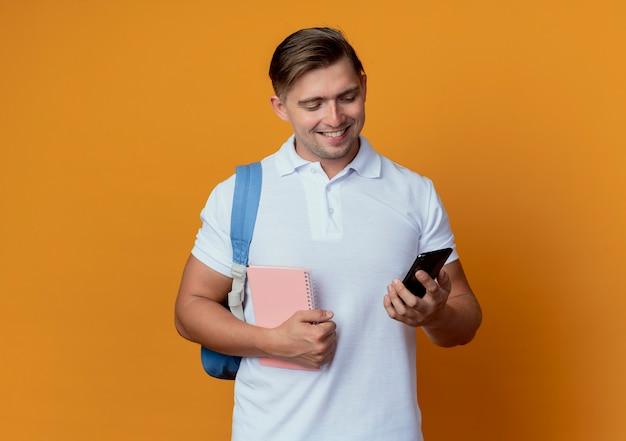 Sorridente giovane studente maschio bello che indossa il taccuino della tenuta della borsa posteriore e che esamina il telefono nella sua mano isolata sull'arancio