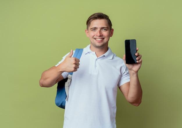 オリーブグリーンの背景で隔離の携帯電話を保持しているバックバッグを身に着けている若いハンサムな男子学生