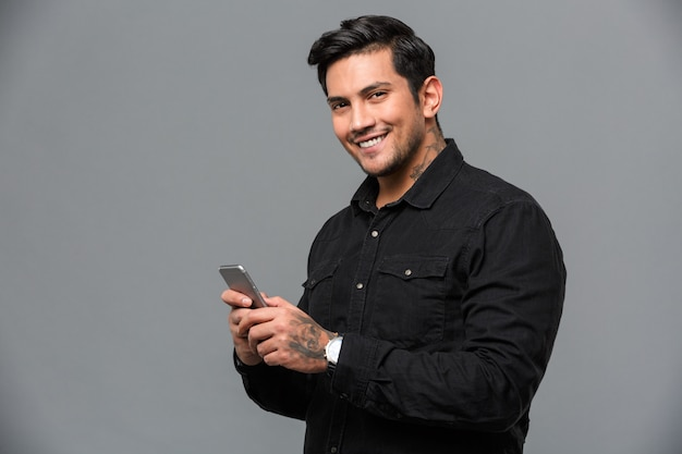 Smiling young handsome man chatting by mobile phone.
