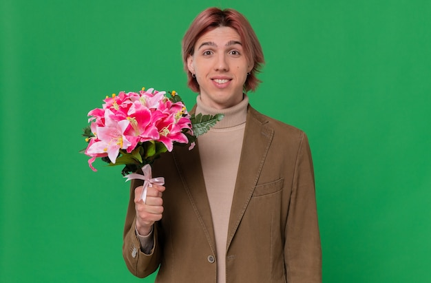 Smiling young handsome man holding bouquet of flowers
