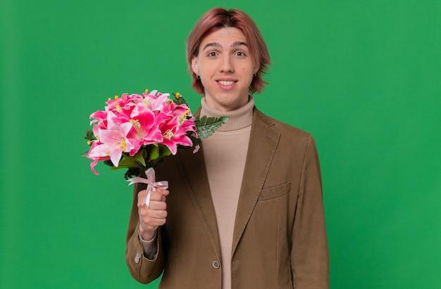 꽃의 꽃다발을 들고 웃는 젊은 잘생긴 남자