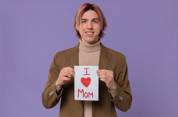 Sorridente giovane uomo bello che tiene una lettera per sua madre. buona festa della mamma