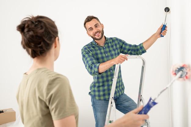 妻と部屋を改造しながらペイントローラーで壁を痛める若いハンサムな男の笑顔