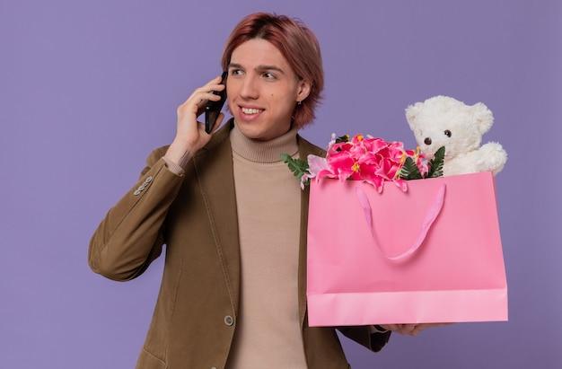 웃고 있는 젊고 잘생긴 남자가 전화 통화를 하고 옆을 바라보는 꽃과 테디베어가 든 분홍색 선물 가방을 들고