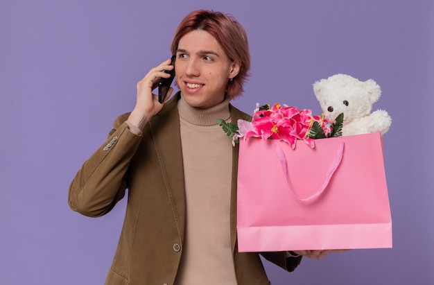 Smiling young handsome man talking on phone and holding pink gift bag with flowers and teddy bear looking at side