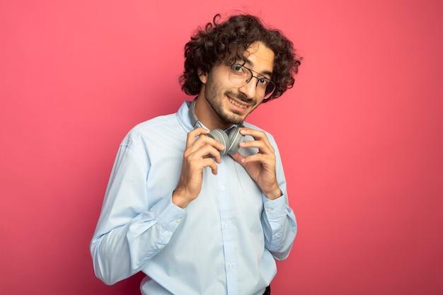ピンクの壁に分離された正面をつかむヘッドフォンを見て首に眼鏡とヘッドフォンを身に着けている若いハンサムな男の笑顔