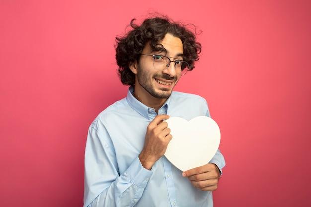 Sorridente giovane uomo bello con gli occhiali che tengono a forma di cuore guardando davanti isolato sul muro rosa