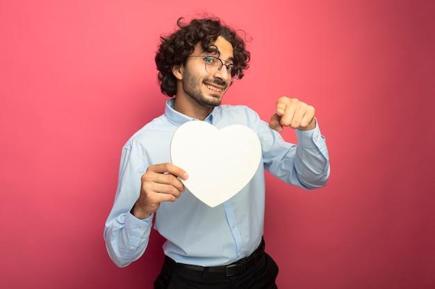 Sorridente giovane uomo bello con gli occhiali che tengono a forma di cuore guardando e indicando davanti isolato sul muro rosa