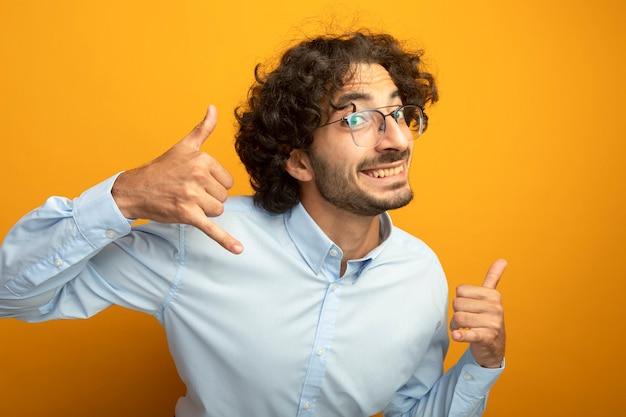 オレンジ色の壁に分離された呼び出しジェスチャーをしている正面を見て眼鏡をかけて笑顔の若いハンサムな男