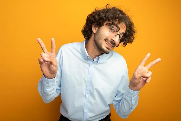 オレンジ色の壁に分離されたピースサインをやって正面を見て眼鏡をかけて笑顔の若いハンサムな男
