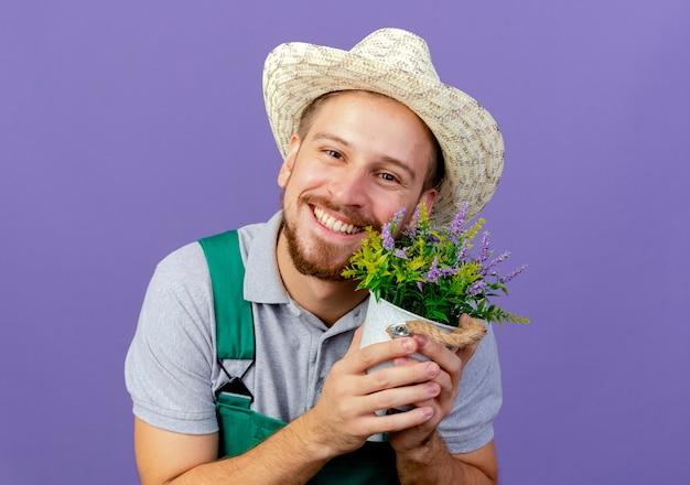 제복을 입은 젊은 잘 생긴 슬라브 정원사와 화분을 들고 모자 복사 공간이 보라색 벽에 고립 된 찾고 웃고