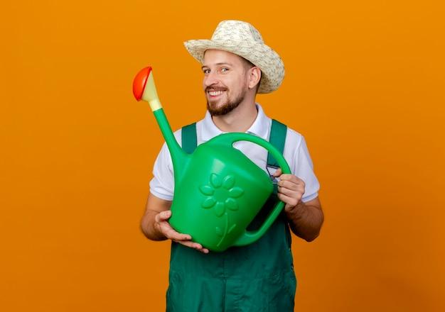 제복을 입은 젊은 잘 생긴 슬라브 정원사 웃고 모자를 들고 물을 수 있습니다.