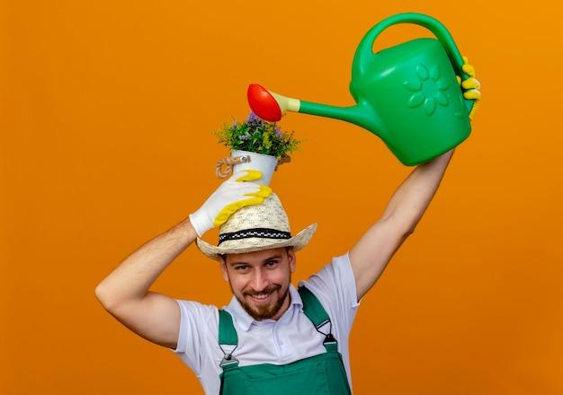 제복을 입은 젊은 잘 생긴 슬라브 정원사 웃고 모자와 원예 장갑 머리에 화분을 들고 물을 수로 물을 수 있습니다.
