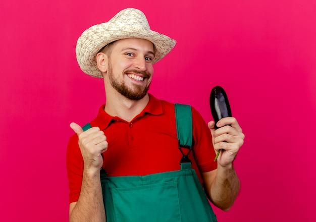 Sorridente giovane giardiniere slavo bello in uniforme e cappello in possesso di melanzane cercando di mostrare il pollice in su