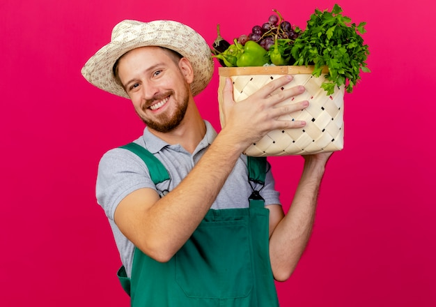 Smiling young handsome slavic gardener in uniform and hat holding basket of vegetables near head looking