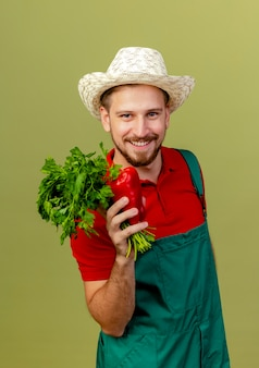 Sorridente giovane giardiniere slavo bello in uniforme e cappello che tiene coriandolo e pepe alla ricerca