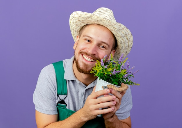 Sorridente giovane giardiniere slavo bello in uniforme e cappello che tiene vaso di fiori che sembra isolato sulla parete viola con lo spazio della copia