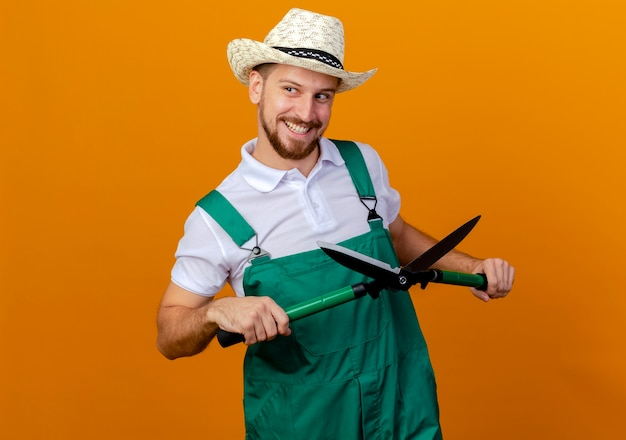 Smiling young handsome slavic gardener in uniform and hat holding pruners looking at side isolated