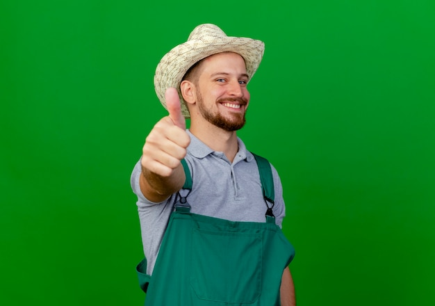 Smiling young handsome slavic gardener in uniform and hat looking showing thumb up