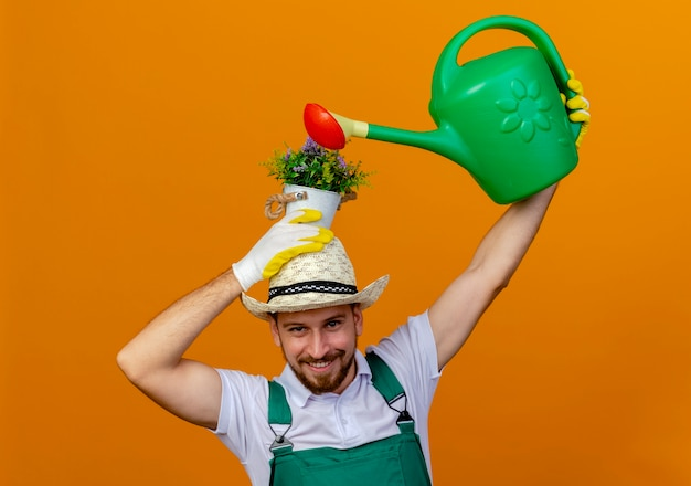 Sorridente giovane giardiniere slavo bello in uniforme che indossa cappello e guanti da giardinaggio tenendo il vaso di fiori sulla testa e innaffiandolo con annaffiatoio mentre guarda isolato