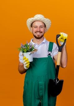 Sorridente giovane giardiniere slavo bello in uniforme che indossa cappello e guanti da giardinaggio che tengono vanga e vaso di fiori che sembrano isolati sulla parete arancione