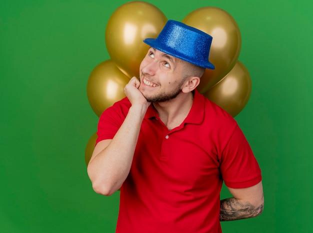 Ragazzo sorridente bello partito slavo che indossa il cappello del partito che tiene palloncini dietro la schiena mettendo la mano sul mento cercando isolato su sfondo verde con spazio di copia