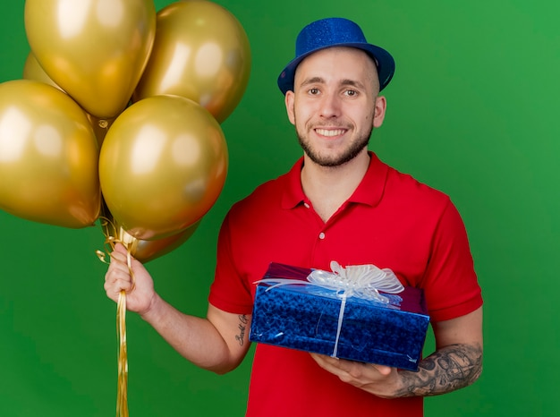Smiling young handsome slavic party guy wearing party hat holding balloons and gift pack looking at camera isolated on green background