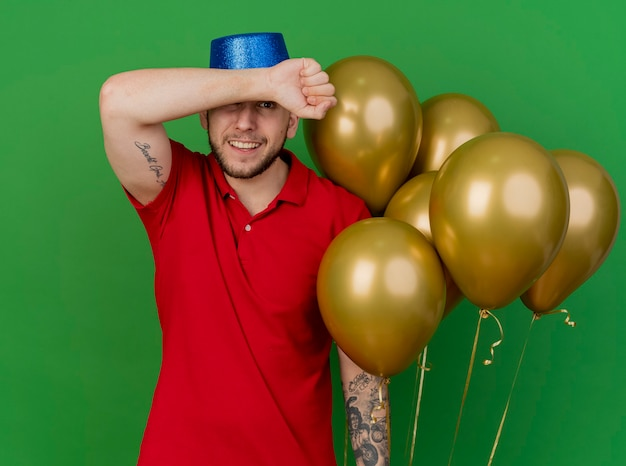 Smiling young handsome slavic party guy wearing party hat holding balloons keeping arm in front of forehead looking at camera isolated on green background