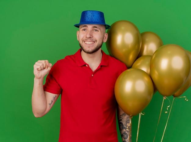 녹색 배경에 고립 예 제스처를하고 측면을보고 풍선을 들고 파티 모자를 쓰고 웃는 젊은 잘 생긴 슬라브 파티 남자