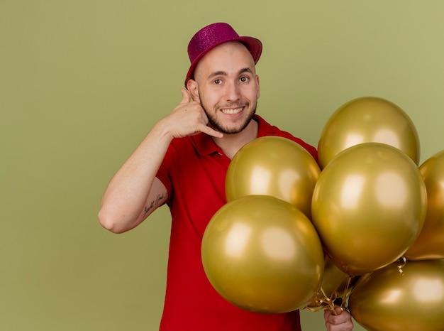 Sorridente giovane ragazzo bello slavo partito indossando il cappello del partito che tiene palloncini guardando la telecamera facendo gesto di chiamata isolato su sfondo verde oliva con lo spazio della copia