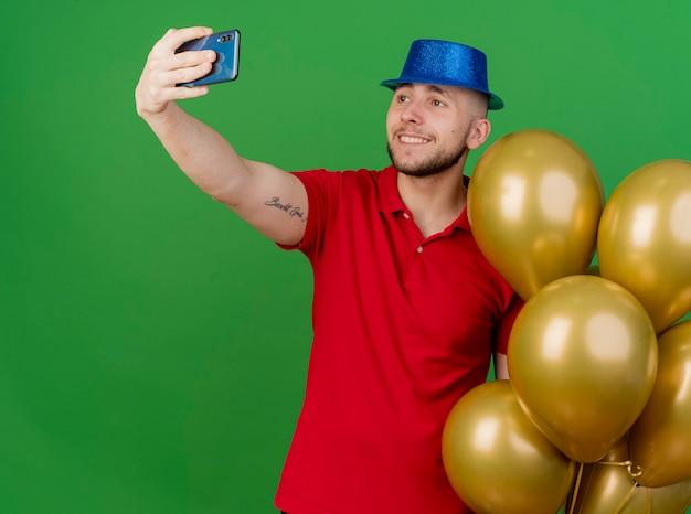 緑の背景で隔離のselfieを取る風船を保持しているパーティー帽子をかぶって若いハンサムなスラブ党の男を笑顔