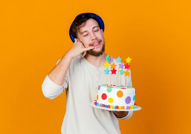 コピースペースでオレンジ色の背景に分離された目を閉じてコールジェスチャーをしている星とバースデーケーキを保持しているパーティーハットを身に着けている若いハンサムなスラブ党の男を笑顔