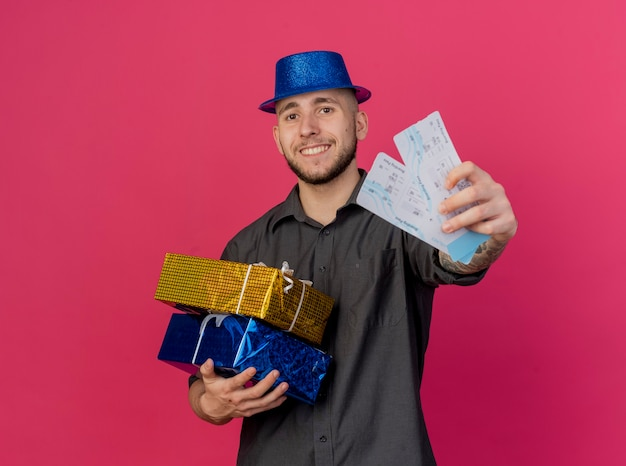 Smiling young handsome slavic party guy wearing party hat holding gift packs looking at camera stretching out airplane tickets towards camera isolated on crimson background with copy space