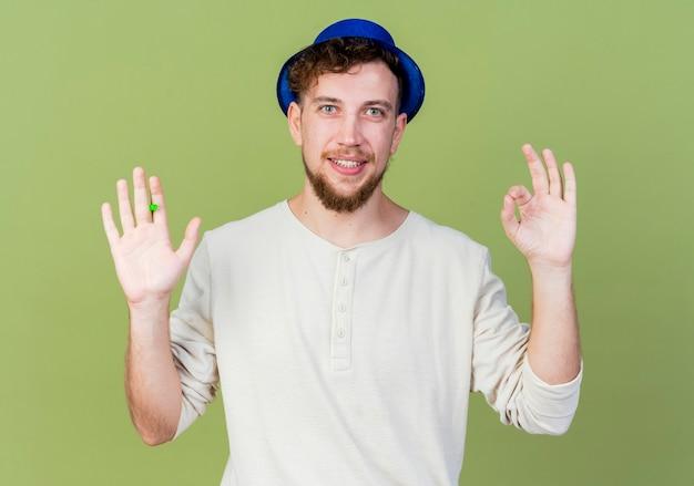 올리브 녹색 배경에 고립 된 확인 서명을 하 고 카메라를보고 파티 송풍기를 들고 파티 모자를 쓰고 젊은 잘 생긴 슬라브 파티 남자 미소