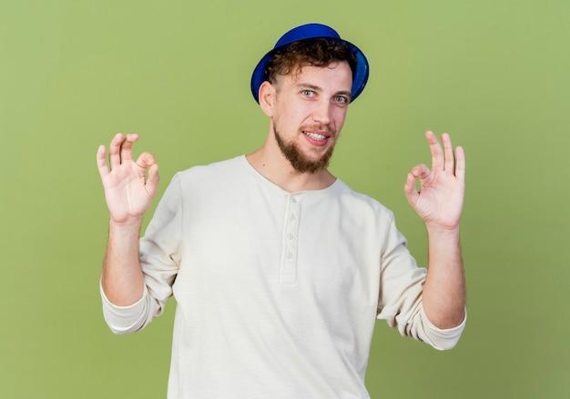 올리브 녹색 배경에 고립 된 확인 표시를하고 카메라를보고 파티 모자를 쓰고 젊은 잘 생긴 슬라브 파티 남자 미소