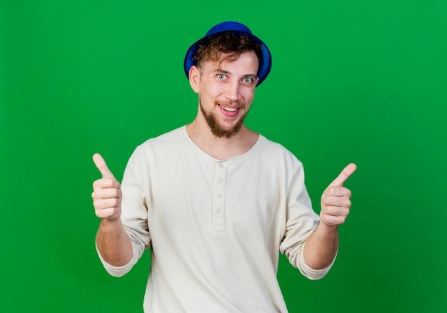 녹색 배경에 고립 엄지 손가락을 보여주는 카메라를보고 파티 모자를 쓰고 웃는 젊은 잘 생긴 슬라브 파티 남자