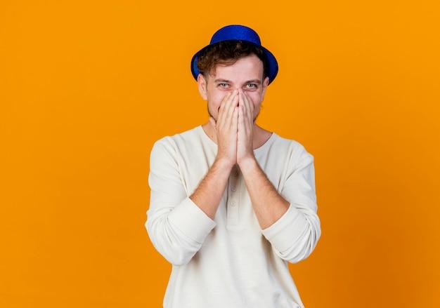 Sorridente giovane ragazzo bello partito slavo indossando il cappello del partito che guarda l'obbiettivo tenendo le mani sulla bocca isolato su sfondo arancione con spazio di copia