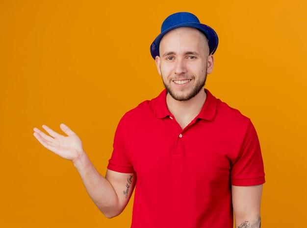 Ragazzo sorridente bello partito slavo che indossa il cappello del partito che guarda l'obbiettivo che mostra la mano vuota isolata su fondo arancio