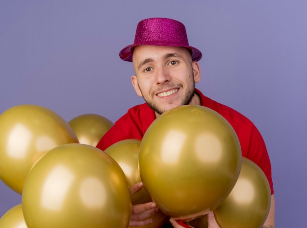 Smiling young handsome slavic party guy wearing party hat standing among balloons touching them looking at camera isolated on purple background